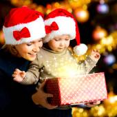 Mother with child opens the box with gifts on christmas — Stockfoto