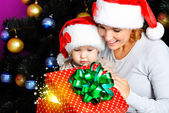 Mother with little child open gifts on christmas — Foto de Stock