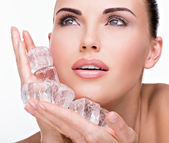 Beautiful woman applies ice to face — Stock Photo