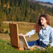 Young painter at work in the mountains — Stock Photo #58219263