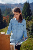 Young painter at work in the mountains — Stockfoto
