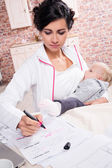 Young mother working with her baby — Stock Photo