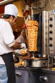 Cook slices meat from spit — Stockfoto