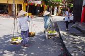 Two women carrying fruit  — Stok fotoğraf