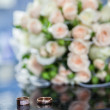 Wedding rings and bouquet on the table — Stock Photo #67029319