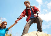 Hiker reaches hand to woman — Stock Photo