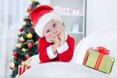 Boy in santa suit with Christmas present — Stock Photo