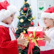 Small children give gifts at Christmas — Stock Photo #58670151
