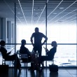 Silhouettes of businesspeople in business centre — Stock Photo #64981625