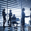 Silhouettes of businesspeople in office — Stock Photo #64981741