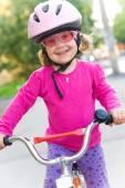 Little girl in helmet on bicycle — Stock Photo