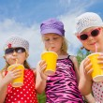 Three little girls drink cocktails — Stock Photo #76059501