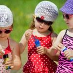 Three little girls blow bubbles — Stock Photo #76059507