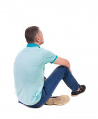 Back view of seated handsome man in polo looking up. — Stock Photo