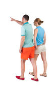Back view of walking young couple (man and woman) pointing. — Stock fotografie
