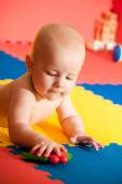 Closeup of happy six months baby boy crawling on colorful playma — Stock Photo