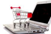 Shopping cart over a laptop — Stock Photo