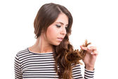 Young woman looking at her hair — Stock Photo