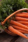 Fresh carrots in wicker basket — Stockfoto