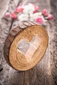 Heart hole in wood and flowers — Stok fotoğraf