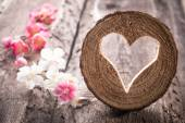 Heart hole in wood and flowers — Stock Photo