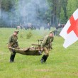 Постер, плакат: Men of medical squad move a wounded soldier