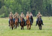 Cavalry soldiers ride on horses across the field — Stock Photo