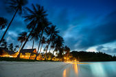 Bungalows, palms and beach at sunset in thailand paradise — Stock Photo