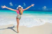 Long haired blonde woman with flower in hair in bikini on tropical beach — Stock Photo