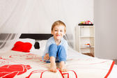 Smiling boy sitting on parents bed — Stock Photo