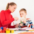 Mother helping her child to cut paper — Stock Photo #77558204