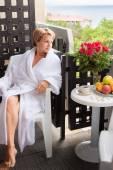 Jeune femme assise sur un balcon avec une tasse de café dans le mor — Photo