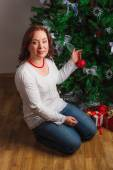 Woman sitting nearby fir-tree — Stock Photo