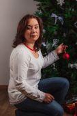 Nice woman decorating  Christmas tree — Stock Photo
