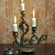 Antique candelabra with three melting candles on an old wallpape — Foto Stock #73525677