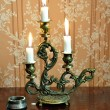 Antique candelabra with three melting candles on an old wallpape — Foto Stock #73525683