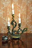 Antique candelabra with three melting candles on an old wallpape — Stock Photo