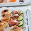 Canapes with assorted cold meat on a buffet — Stock Photo #52864837