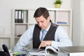 Middle Age Businessman Seriously Reading a folder at the Table. — Stock Photo