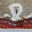 Wedding Cake Topped with Bride and Groom Figurines — Stock Photo #57711621
