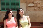 Smiling Women Sitting on a Bench Looking Up — Stock Photo