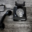 Black rotary telephone with the receiver off-hook — Stock Photo #73005357