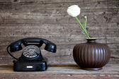 Rotary telephone next to a white carnation flower — Stock Photo