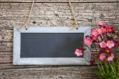 Blank rectangular blackboard on rustic wooden wall — Stock Photo
