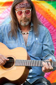 Bearded middle-aged hippie man playing the guitar — Stock Photo