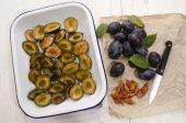 Cut plums in an enamel bowl — Stok fotoğraf