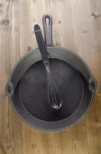 Used cast iron pan an whisk — Stock Photo