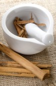 Mortar and pestle with cinnamon on jute — Stock Photo