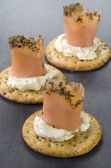 Salmon rolls with soft cheese on cracker — Stock Photo