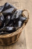 Fresh and uncleaned mussels in a wicker basket — Stock Photo